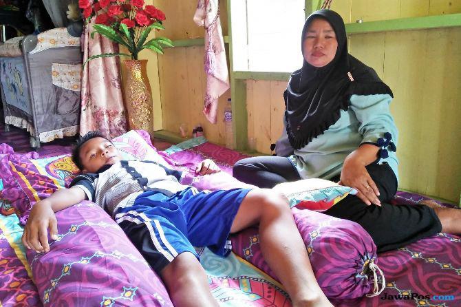 Rasimah, 37, saat merawat buah hatinya YP di kediamannya di Desa Teluk Dawan, Kecamatan Muara Sabak Barat, Kabupaten Tanjung Jabung Timur, Jambi, Senin, 9 Juli 2018. (Foto: Joni Hartanto/Jambi Ekspres/Jawa Pos Group)