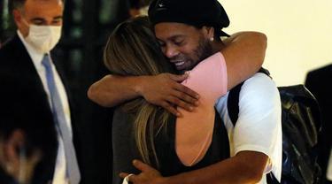 Mantan pemain timnas Brasil, Ronaldinho dipeluk oleh seorang wanita ketika tiba di sebuah hotel untuk menjalani tahanan rumah di Asuncion, Paraguay, Selasa (7/4/2020). Ronaldinho kini berstatus tahanan kota setelah dibebaskan dari penjara dengan membayar uang jaminan. (AP/Jorge Saenz)