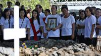 Keluarga dan kerabat korban bom gereja Surabaya berdoa pada pemakaman Martha Djumani di komplek Taman Makam Keputih, Surabaya, Rabu (16/5). Martha merupakan korban bom bunuh diri di Gereja Pantekosta Pusat Surabaya Minggu (13/5) lalu. (AP/Achmad Ibrahim)