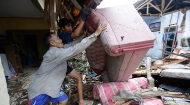 Warga lokal Alimin membersihkan puing-puing dari rumahnya setelah tsunami di Carita, Banten, Kamis, (27/12). Pemerintah telah memperluas zona larangan di sekitar pulau gunung berapi pulau yang memicu tsunami. (AP Photo/Achmad Ibrahim)