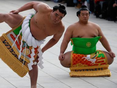 Juara sumo asal mongolia, Yokozuna Hakuho (kiri) melakukan persiapan untuk ritual tahunan di Kuil Meiji di Tokyo, Jepang, (7/1). Ritual ini dalam perayaan tahun baru 2016. (REUTERS / Yuya Shino)