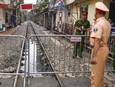 Polisi berjaga dekat barikade rel kereta yang populer sebagai lokasi selfie di Hanoi, Vietnam, Kamis (10/10/2019). Pihak berwenang menutup kafe yang berjajar di pinggir rel kereta tersebut dengan alasan keamanan. (Nhac NGUYEN/AFP)