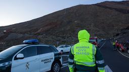 Aparat keamanan berjaga di lereng Gunung El Teide (3.718 meter) di Taman Nasional El Teide, Pulau Canary, Spanyol, Rabu (15/3). Sekitar 60 wisatawan terperangkap di dua kereta gantung saat menuju puncak Gunung El Teide (3.718 meter). (Desiree Martin/AFP)