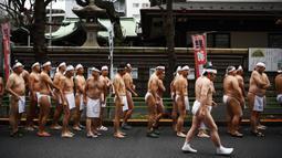 Orang-orang percaya Shinto dari Kuil Teppozu Inari mengelilingi kuil untuk melakukan pemanasan sebelum mandi di air dingin untuk memurnikan jiwa dan tubuh mereka selama ritual Tahun Baru di Tokyo (12/1/2020).  (AFP/Charly Triballeau)