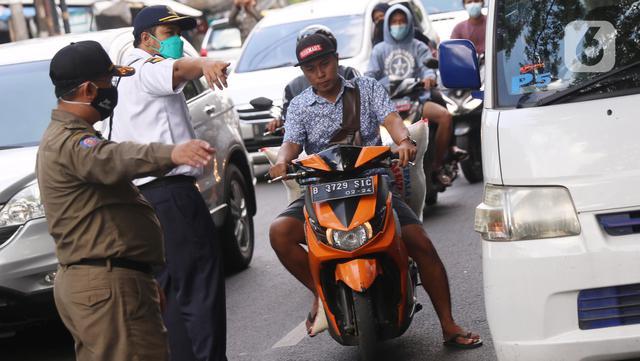 Petugas mengarahkan warga yang terjaring razia penggunaan masker di Kelurahan Sudimara Barat, Kota Tangerang, Kamis (27/5/2021). Mereka yang terjaring razia diminta untuk melakukan tes GeNose C19 guna mencegah penularan virus corona Covid-19. (Liputan6.com/Angga Yuniar)