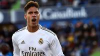 Bek Real Madrid, Raphael Varane, merayakan gol yang dicetaknya ke gawang Getafe pada laga La Liga Spanyol di Stadion Col Alfonso Perez, Getafe, Sabtu (4/1). Getafe kalah 0-3 dari Madrid. (AFP/Oscar Del Pozo)