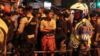 Polisi menjaga ketat sekitar lokasi baku tembak di Jalan Kaliurang km 9.5, Ngaglik, Yogyakarta, Sabtu (14/7). Baku tembak antara polisi dan orang atau kelompok yang belum diketahui terjadi sekitar pukul 17.00 WIB. (Liputan6.com/Helmi Fithriansyah)
