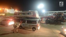 Pekerja dibantu alat berat menarik gerbong kereta Light Rail Transit (LRT) di Pelabuhan Car Terminal, Tanjung Priok, Jakarta, Jumat (13/4). LRT ini akan dipergunakan dalam perhelatan Asian Games 2018 pada Agustus mendatang.  (Merdeka.com/Imam Buhori)