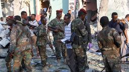 Pasukan keamanan berjaga di lokasi ledakan di luar Hotel Weheliye, Mogadishu, Somalia, (22/3). Mereka mengklaim telah menargetkan pertemuan pejabat pemerintah, tentara dan perwira intelijen. (AP Foto/Farah Abdi Warsameh)