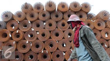 Seorang buruh melintas di depan besi baja di Pelabuhan Sunda Kelapa, Jakarta Utara, Selasa (9/8). Harga besi mengalami kenaikan sekitar 30%. Kenaikan terjadi sejak awal bulan Maret lalu hingga saat ini. (Liputan6.com/Angga Yuniar)
