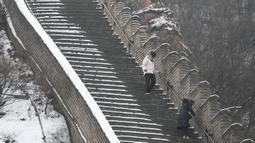 Dua wisatawan menuruni anak tangga saat menikmati liburan musim dingin di Tembok Besar China yang diselimuti salju di utara Beijing (6/1/2020). (AFP/Greg Baker)