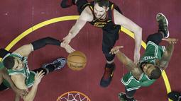 Pemain Cavaliers, Kevin Love (tengah) berebut bola dengan dua pemain Boston pada gim keempat final Wilayah Timur NBA basketball di Quicken Loans Arena (21/5/2018). Cavaliers menang 111-102. (AP/Tony Dejak)