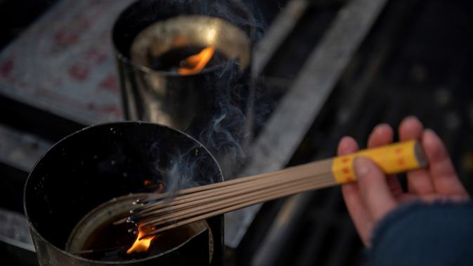 Seorang wanita membakar dupa untuk berdoa keberuntungan pada hari kelima Tahun Baru Imlek di Yonghegong, atau Kuil Lama di Beijing (9/2). Warga China merayakan Tahun Babi tersebut dengan doa, pesta keluarga, dan belanja. (AFP Photo/Nicolas Asfouri)#source%3Dgooglier%2Ecom#https%3A%2F%2Fgooglier%2Ecom%2Fpage%2F%2F10000