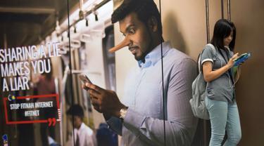 Penumpang menunggu kedatangan kereta di sebelah iklan tentang larangan penyebaran hoax atau berita bohong di Stasiun Kereta Kuala Lumpur, Malaysia, Kamis (29/3). Pemerintah Malaysia mengesahkan undang-undang (UU) Antihoax. (AP Photo/Vincent Thian)