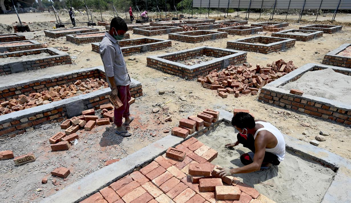 Para buruh bekerja membangun tempat kremasi di ladang kosong di New Delhi, India, Rabu (5/5/2021). India memperbanyak tempat kremasi karena meningkatnya jumlah kematian akibat virus corona COVID-19. (Money SHARMA/AFP)