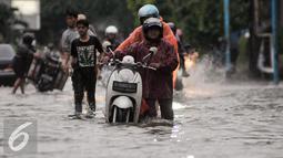 Pengendara mendorong motornya yang mogok akibat menerebos banjir di Jalan Kemang Raya, Jakarta, Jumat (11/11). Hujan deras yang mengguyur wilayah Jakarta menyebabkan banjir di kawasan Jalan Kemang Raya. (Liputan6.com/Yoppy Renato)