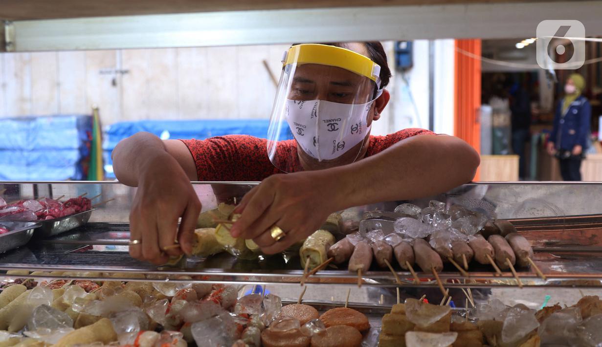 Pedagang mengenakan face sheild atau pelindung wajah saat berjualan di Tangerang, Banten, Rabu (13/5/2020). Penggunaan pelindung wajah tersebut dilakukan untuk mencegah risiko penularan virus corona COVID-19 pada saat berdagang. (Liputan6.com/Angga Yuniar)
