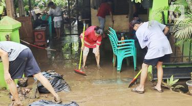 Warga membersihkan lumpur sisa banjir di halaman rumahnya di perumahan Ciledug Indah, Tangerang Senin (21/2/2021). Banjir yang menggenangi perumahan tersebut membuat warga mengalami kerugian cukup besar karena barang-barang berharga mereka rusak parah. (Liputan6.com/Angga Yuniar)