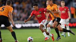 Gelandang Manchester United, Jesse Lingard, berusaha melewati bek Wolverhampton, Ryan Bennett, pada laga Premier League di Stadion Molineux, Wolverhampton, Senin (19/8). Kedua klub bermain imbang 1-1. (AFP/Paul Ellis)