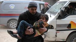 Seorang pria menggendong seorang anak untuk diselamatkan usai terjadi serangan udara dari pasukan Assad di wilayah Ghouta timur, Suriah (6/2). (AFP Photo/Hamza Al-Ajweh)