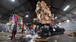 """Seorang pria berdiri di dekat sebuah karya seni jalanan oleh kolektif seniman yang ditampilkan Iretge sebagai bagian dari pameran """"Strokar inside"""" di bekas supermarket di Brussels (5/9). (AFP Photo/Emmanuel Dunand)"""