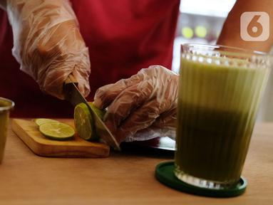 Pekerja membuat ramuan jamu tradisional di kafe Suwe Ora Jamu, kawasan M Bloc, Jakarta, Jumat (10/7/2020). Kafe yang menjadi tempat alternatif nongkrong sehat bagi kawula muda ini menyediakan berbagai jenis ramuan jamu tradisional. (Liputan6.com/Herman Zakharia)
