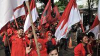 Kader PDIP membawa bendera saat menuju Kantor KPU, Jakarta, Selasa (17/7). Kedatangan anggota PDIP untuk mendaftarkan bakal caleg di KPU diiringi pawai bendera, ondel-ondel, musik hingga wanita cantik. (Merdeka.com/Iqbal S. Nugroho)