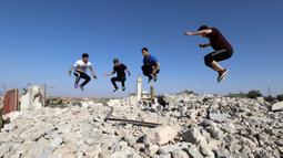 Pemuda Suriah melakukan olahraga ekstrem parkour di atas reruntuhan bangunan yang hancur akibat serangan pasukan rezim di kota Binnish di provinsi barat laut Idlib pada 17 Juni 2020. Parkour merupakan olahraga ketangkasan yang terdiri dari lari, melompat, salto dan berayun. (Abdulaziz KETAZ / AFP)