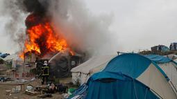 "Petugas memadamkan kobaran api di pengungsian imigran ""Jungle"", di kota pelabuhan Calais, Prancis (26/10). Karena kumuh pemerintah Prancis akhirnya mulai mengosongkan kamp pengungsian imigran tersebut. (REUTERS/Philippe Wojazer)"