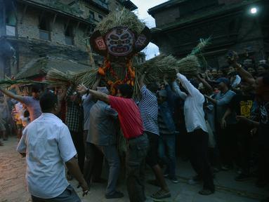 Para lelaki Nepal membawa patung jerami iblis Ghantakarna untuk dibakar dalam festival Ghantakarna di kota kuno Bhaktapur, Nepal (30/7/2019). Festival Hindu ini juga dikenal dengan nama Gathemangal. (AFP Photo/Prakash Mathema)