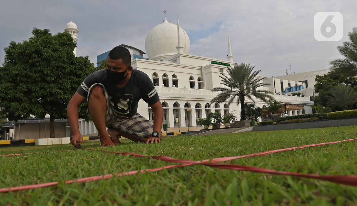Pekerja membuat garis saf sholat Idul Fitri di Masjid Al Azhar, Jakarta, Rabu (11/5/2021). Masjid Al Azhar akan menggelar sholat idul Fitri secara berjamaah di lapangan masjid tersebut dengan protokol pencegahan COVID-19 yang ketat. (Liputan6.com/Herman Zakharia)