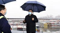Presiden China Xi Jinping saat mengunjungi kawasan pelabuhan Chuanshan di Pelabuhan Ningbo-Zhoushan, Provinsi Zhejiang, China, Minggu (29/3/2020). Xi Jinping melakukan inspeksi terhadap proses dimulainya kembali kegiatan kerja dan produksi di Zhejiang. (Yan Yan/Xinhua via AP)