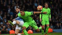 Bernardo Silva menjatuhkan Jeffrey Br pada leg kedua, babak 16 besar Liga Champions yang berlangsung di Stadion Etihad, Manchester, Rabu (13/3). Man City menang 7-0 atas Schalke. (AFP/Paul Ellis)