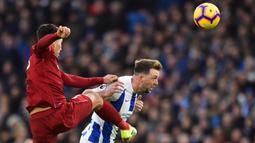 Gelandang Liverpool, Roberto Firmino, berebut bola dengan gelandang Brighton, Dale Stephens, pada laga Premier League di Stadion Vitality, Brighton, Sabtu (12/1). Brighton kalah 0-1 dari Liverpool. (AFP/Glyn Kirk)
