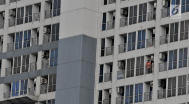 Seorang penghuni apartemen terlihat berdiri di balkon kamarnya di Jakarta, Selasa (16/4). Data Colliers International mencatat pada kuartal I-2019 tambahan pasokan apartemen sebanyak 1.847 unit. Sehingga total apartemen di Jakarta saat ini sebanyak 203.664 unit. (merdeka.com/Iqbal S. Nugroho)