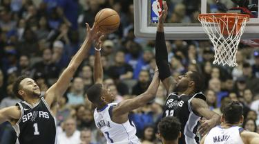 Aksi pemain Dallas Mavericks, Dennis Smith Jr. (1) mencoba mencetak poin saat diadang pemain San Antonio Spurs pada laga NBA Basketball game di American Airlines Center, Dallas, (14/11/2017). Spurs menang 97-91. (AP/LM Otero)