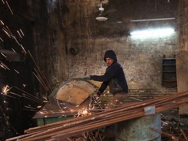 Seorang pekerja memotong besi di sebuah bengkel di Baghdad, Irak (20/2). Para pandai besi ini bekerja untuk membuat pasak tenda dan alat-alat pertanian. (AFP Photo/Ahmad Al-Rubaye)