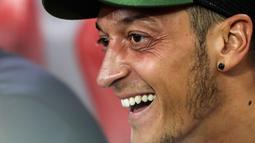 Gelandang Arsenal, Mesut Ozil tersenyum di bangku cadangan saat melihat rekannya bertanding melawan Atletico Madrid di International Champions Cup di Singapura (26/7). Arsenal kalah 3-1 setelah bermain 1-1 di waktu normal. (AP Photo/Yong Teck Lim)