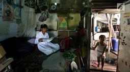 Siswi SD belajar di kamarnya yang berada di kawasan padat penduduk, Kapuk, Jakarta, Senin (26/3). Gubernur DKI Jakarta Anies Baswedan mengatakan kebanyakan penduduk Jakarta mengontrak atau menyewa. (Liputan6.com/JohanTallo)