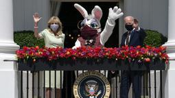 Presiden Joe Biden bersama Ibu Negara Jill Biden dan Kelinci Paskah melambaikan tangan dari balkon Ruang Biru, Gedung Putih, Washington, Amerika Serikat, Senin (5/4/2021). Gedung Putih kembali meniadakan tradisi Easter Egg Roll menyusul pandemi COVID-19 yang sedang berlangsung. (AP Photo/Evan Vucci)