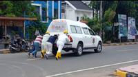Tenaga Medis PSC Mamuju mendorong mobil ambulance yang mogok ketika akan menjemput pasien Covid-19 (Liputan6.com/Abdul Rajab Umar)