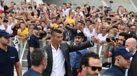 Para suporter menyambut kedatangan bintang baru Juventus, Cristiano Ronaldo, saat tiba untuk menjalani tes kesehatan di area Stadion Allianz, Turin, Senin (17/7/2018). CR 7 hijrah dari Real Madrid ke Juventus. (AFP/Miguel Medina)