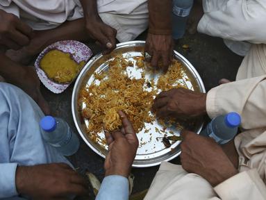 Warga berbuka puasa bersama selama bulan suci Ramadan di Karachi, Pakistan, Selasa (12/5/2020). Warga berbuka puasa bersama setelah pemerintah melonggarkan lockdown terkait pandemi virus corona COVID-19. (AP Photo/Fareed Khan)