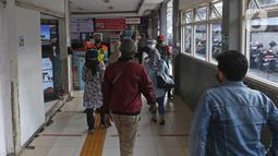 Sejumlah calon penumpang KRL Commuterline menjalani pengecekan suhu tubuh saat akan masuk Stasiun Depok Lama, Depok, Jawa Barat, Selasa (9/6/2020). Stasiun Depok Lama terpantau lengang pada hari kedua dibukanya aktivitas perkantoran di Jakarta pada masa transisi PSBB. (Liputan6.com/Herman Zakharia)