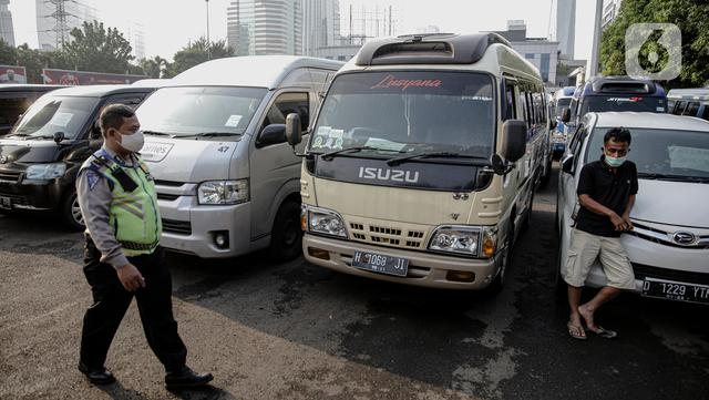 Polisi berjalan melewati kendaraan travel gelap yang disita jajaran Direktorat Lalu Lintas Polda Metro Jaya, Jakarta, Kamis (29/4/2021). Sebanyak 115 kendaraan travel gelap diamankan karena diduga kuat mengangkut pemudik di tengah masa pengetatan larangan mudik 2021. (Liputan6.com/Faizal Fanani)