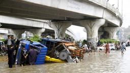 Kendaraan terguling setelah hujan monsun mengguyur deras di Kota Karachi, Pakistan, 25 Agustus 2020. Hujan deras membuat kekacauan di beberapa bagian kota tersebut, dengan air hujan menyebabkan banjir serta merendam jalan, kendaraan, maupun area-area berdataran rendah. (Xinhua/Str)