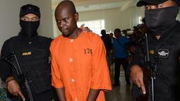 Warga Negara Tanzania, Abdul Rachman Azman dikawal petugas sebelum konferensi pers di Kantor Pelayanan Bea Cukai Bandara Ngurah Rai, Bali, Selasa (12/2). Abdul ditangkap karena menyelundupkan methamphetamine 1,13 kg di dalam perutnya (Sonny TUMBELAKA/AFP)