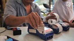 Petugas menggesek KJP milik salah seorang warga saat membeli sembako murah di Pasar Blok G Tanah Abang, Jakarta, Selasa (11/12). (Merdeka.com/Iqbal S. Nugroho)