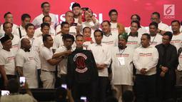 Aktivis 98 Adian Napitupulu memberikan jaket bertuliskan Son Of Democracy Indonesia 98 kepada Presiden Joko Widodo selama acara Halalbihalal bersama aktivis 98 di Jakarta, Minggu (16/6/2019). (Liputan6.com/Angga Yuniar)