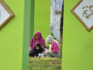 Warga berdoa saat melakukan ziarah di Kuburan Massal Ulee Lheue selama peringatan 14 tahun tsunami Aceh di Banda Aceh, Rabu (26/12). Sejumlah warga mengenang keluarga yang meninggal akibat bencana tsunami di Aceh 14 tahun silam. (Chaideer MAHYUDDIN / AFP)